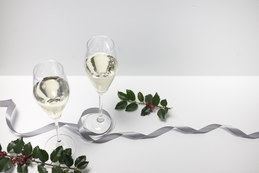two champagne glasses on a white tablecloth with holly branches, red berries and silver ribbon